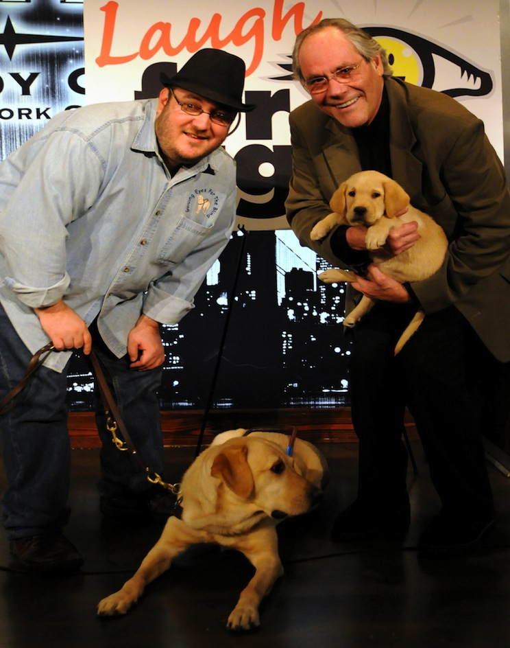Photo of Brian Fischler with his guide dog Nash and Robert Klein with a Guiding Eyes for the Blind puppy in training